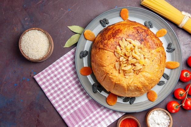 Vista de cima, a deliciosa refeição oriental do shakh plov consiste em arroz cozido dentro de uma massa redonda em uma superfície escura.
