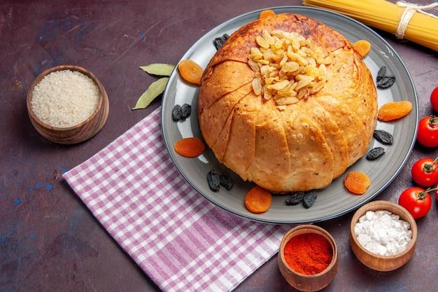 Vista de cima, a deliciosa refeição oriental do shakh plov consiste em arroz cozido dentro de uma massa redonda na mesa escura.