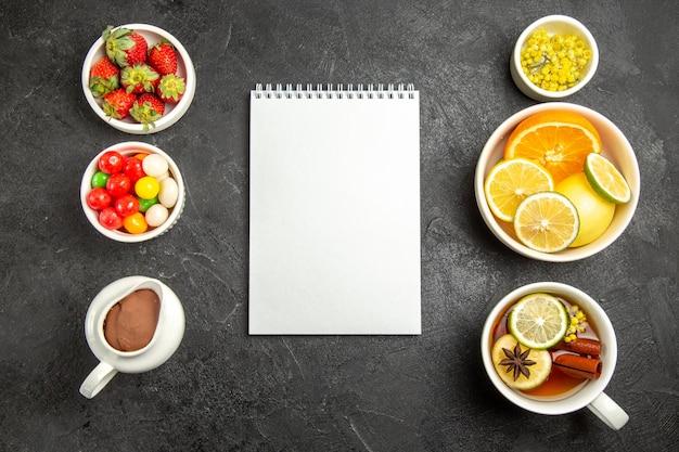 Vista de cima à distância doces com chá uma xícara de chá com canela e anis estrelado ao lado do caderno branco e as tigelas de ervas cítricas, frutas cítricas, chocolate, creme, morangos na mesa