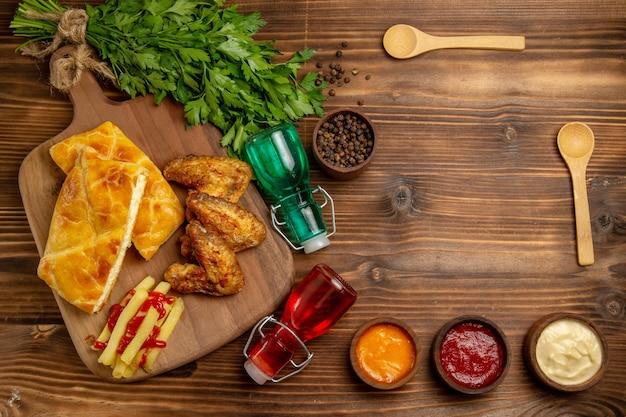 Vista de cima à distância, ervas fastfood, batatas fritas apetitosas, frango e torta no quadro ao lado das colheres de especiarias, frascos e ervas