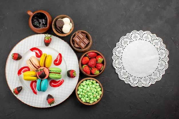 Vista de cima à distância. prato de morangos e macaroons de apetitosos macarons franceses e taças de doces de morangos em volta e guardanapo de renda na mesa