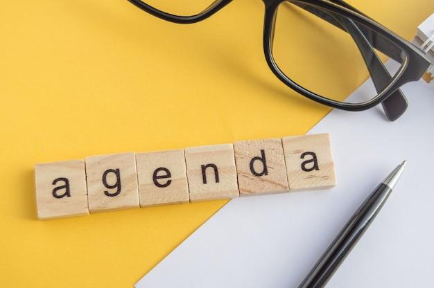 Vista de cima a palavra da agenda escrita em cubos de madeira na área de trabalho com óculos, caneta, bloco de notas de papel em uma parede amarela, vista de cima, layout plano, estilo empresarial.