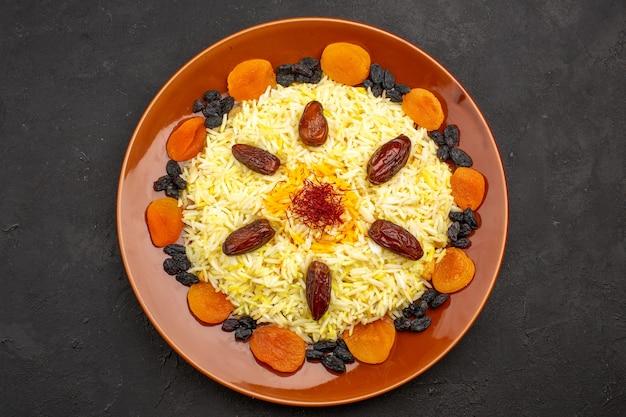 Vista de cima, a saborosa refeição oriental famosa consiste em arroz cozido e passas no escuro Foto gratuita