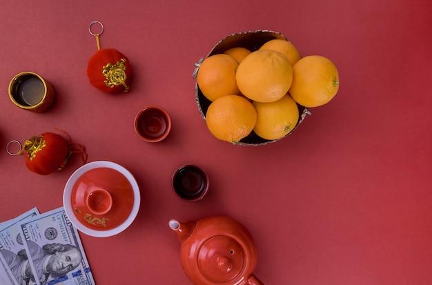 Vista de cima acessórios decorações do festival de ano novo chinês de pacote vermelho de folhas de tangerinas e dinheiro em dólares americanos boa sorte