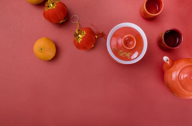 Vista de cima acessórios decorações do festival de ano novo chinês de tangerinas decoração de folha vermelha no chá