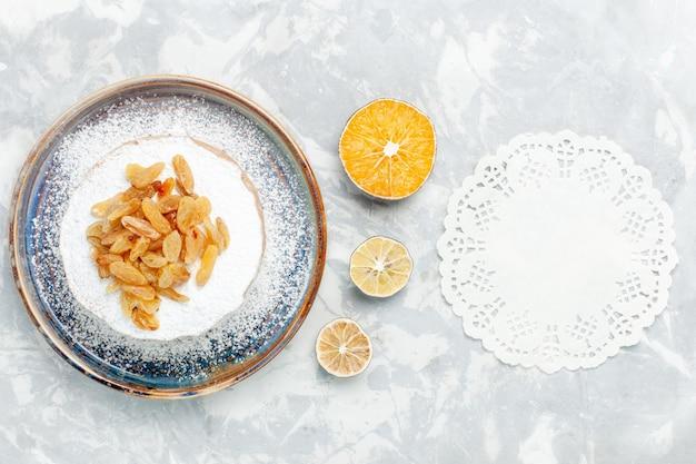Vista de cima, açúcar em pó, passas e uvas secas em cima de um pequeno bolo dentro do prato na mesa branca