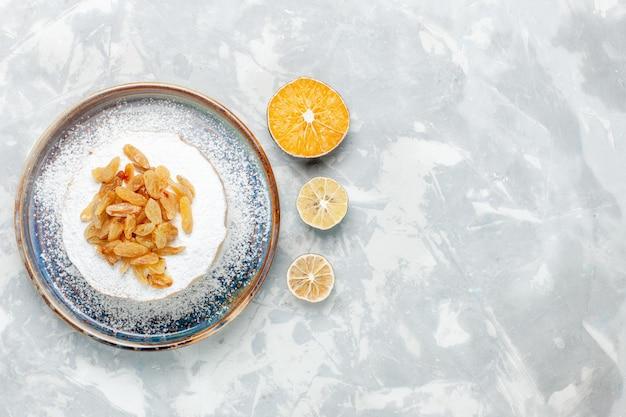 Vista de cima, açúcar em pó, passas, uvas secas em cima de um pequeno bolo dentro do prato na superfície branca