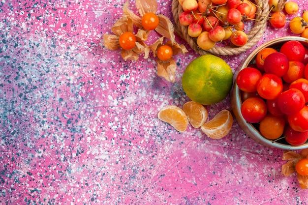 Vista de cima, ameixas azedas frescas frutas maduras dentro de um pratinho com cerejas e tangerina na mesa rosa.