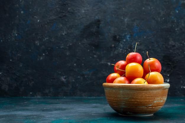 Vista de cima ameixas frescas frutas ácidas e maduras dentro de uma pequena panela no fundo azul escuro frutas suaves vitamina fresca