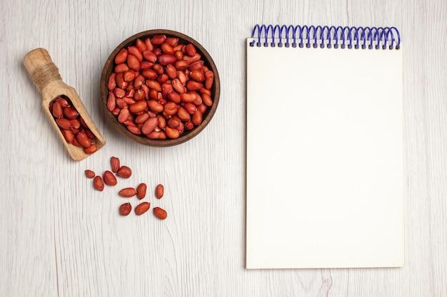Vista de cima amendoins frescos e limpos dentro do prato no branco nozes de mesa, muitas plantas de árvore, lanche