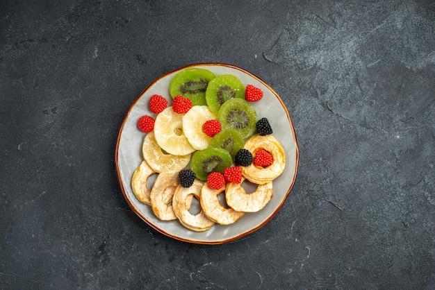 Vista de cima anéis de abacaxi secos com kiwis secos e maçãs na superfície cinza escuro