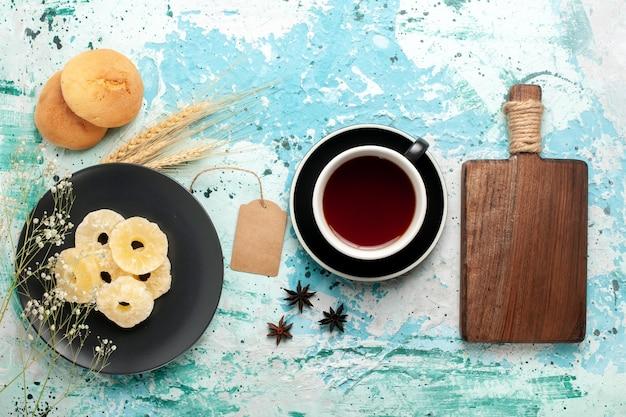 Vista de cima anéis de abacaxi secos com xícara de chá na mesa azul bolo assar biscoito de frutas biscoito doce de açúcar