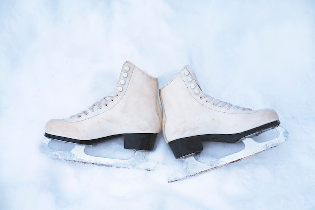 Vista de cima. antigos patins vintage brancos na neve branca