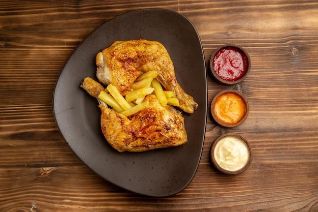 Vista de cima ao longe prato de tigelas de fast food com molhos coloridos ao lado do prato de batatas fritas apetitosas e coxas de frango na mesa de madeira