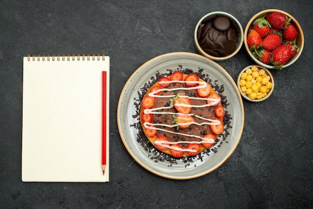 Vista de cima apetitoso bolo de bolo com pedaços de chocolate e morango no prato branco e tigelas de chocolate, morango e avelã ao lado do caderno branco e lápis vermelho na mesa escura