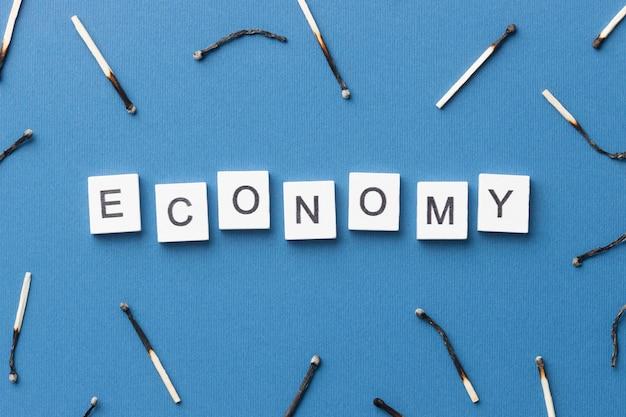 Vista de cima arranjo de fósforos queimados com palavra econômica