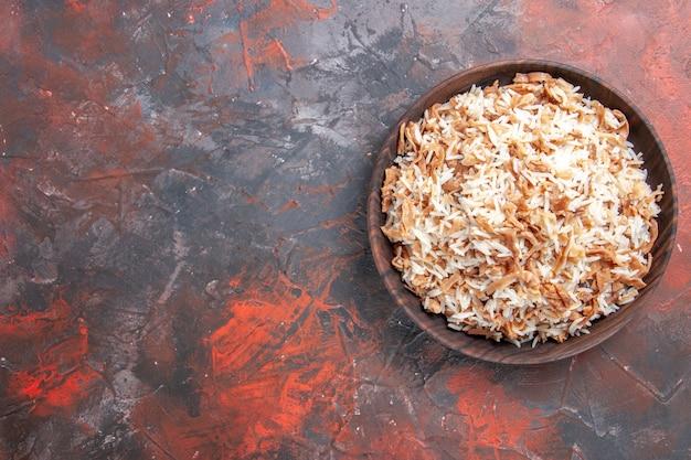 Vista de cima arroz cozido com fatias de massa em massa escura de prato de mesa