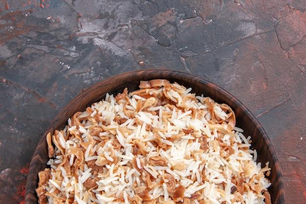Vista de cima arroz cozido com fatias de massa em massa escura de refeição em superfície escura