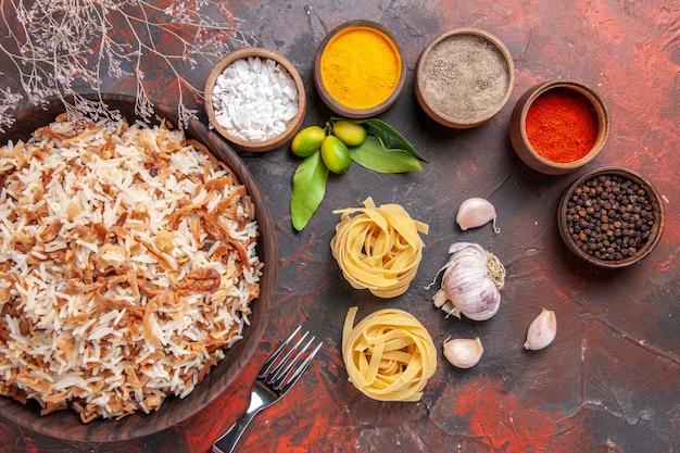 Vista de cima arroz cozido com temperos em superfície escura prato de refeição escuro