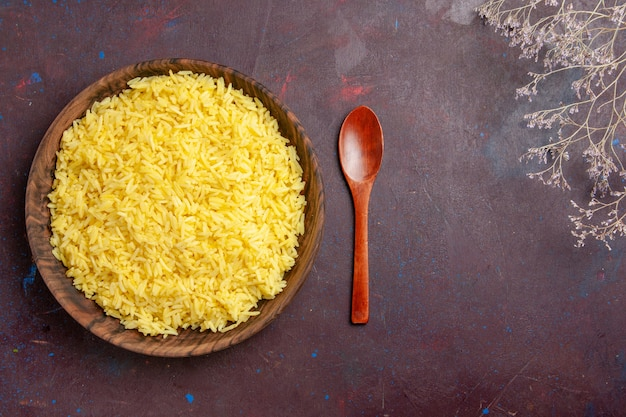 Vista de cima arroz cozido refeição deliciosa dentro de prato marrom em piso escuro refeição com óleo comida arroz jantar