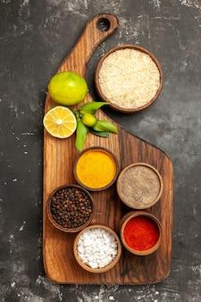 Vista de cima arroz cru com limões e temperos na superfície escura com especiarias frutas crus