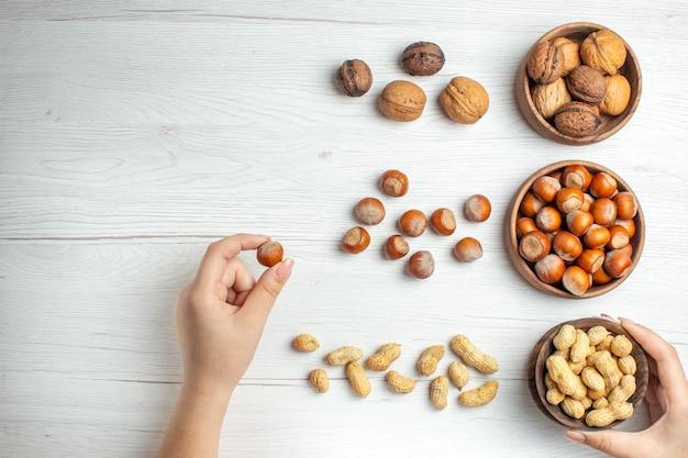 Vista de cima avelãs frescas com amendoim e nozes na mesa branca