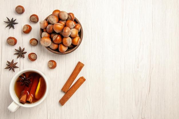 Vista de cima avelãs frescas com uma xícara de chá no chão branco, porca, lanche, bebida, avelã, noz