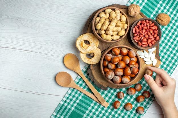 Vista de cima avelãs frescas cruas com amendoim na mesa branca lanche porca planta comida filme nozes pistache