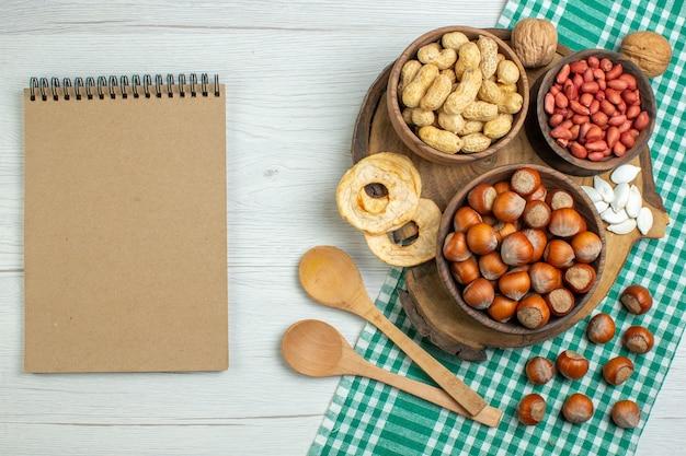 Vista de cima avelãs frescas cruas com amendoim na mesa branca
