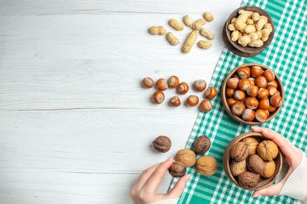 Vista de cima avelãs frescas cruas com nozes e amendoim na mesa branca