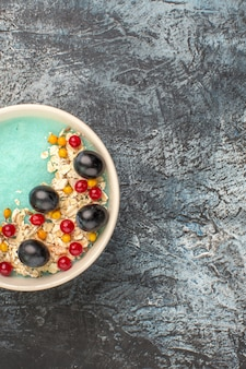 Vista de cima bagas, uvas apetitosas e groselhas na tigela azul