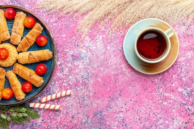 Vista de cima, bagels deliciosos e doces dentro da bandeja com ameixas azedas frescas e chá na mesa rosa claro