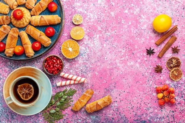 Vista de cima, bagels deliciosos e doces dentro da bandeja com ameixas e xícara de chá na mesa rosa claro