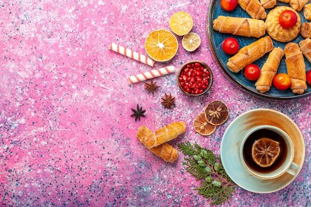 Vista de cima, bagels deliciosos e doces dentro da bandeja com ameixas e xícara de chá na superfície rosa