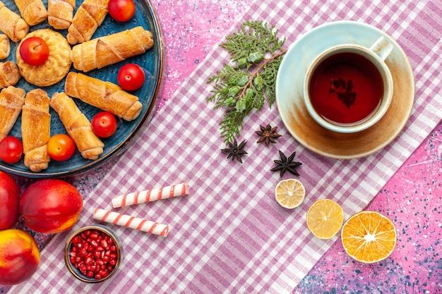 Vista de cima, bagels deliciosos e doces dentro da bandeja com ameixas, pêssegos frescos e xícara de chá na mesa rosa claro
