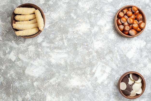 Vista de cima, bagels doces com biscoitos e nozes na superfície branca