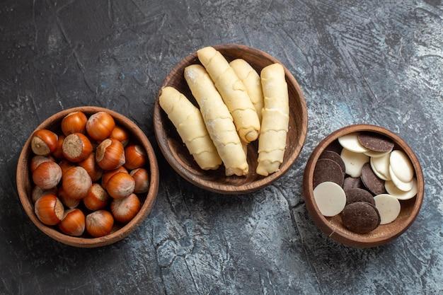 Vista de cima, bagels doces com biscoitos e nozes na superfície escura