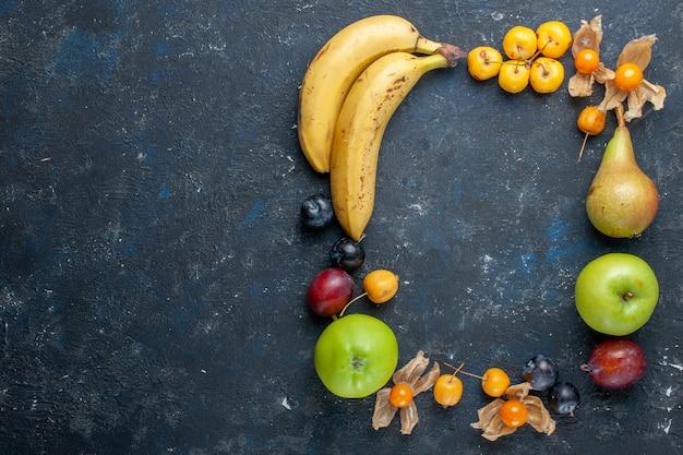 Vista de cima bananas amarelas com maçãs verdes frescas, peras, ameixas e cerejas doces na mesa escura, vitaminas, frutas, bagas, saúde