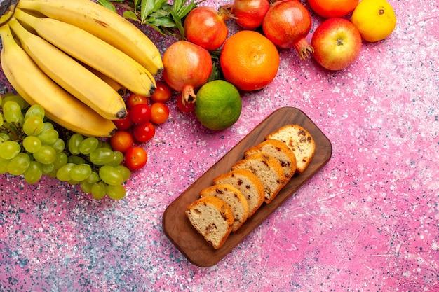 Vista de cima, bananas frescas amarelas deliciosas frutas com bolos de uvas e romãs na mesa rosa