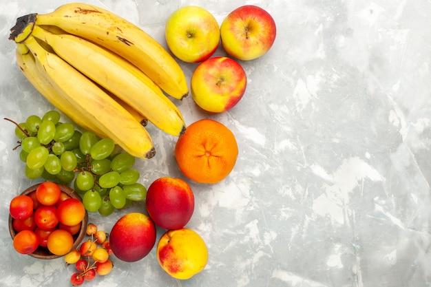Vista de cima, bananas frescas amarelas frutas suaves e deliciosas com uvas e maçãs em uma mesa branca clara