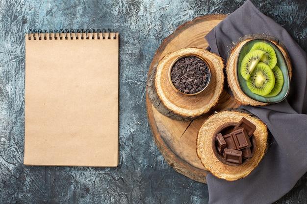 Vista de cima, barras de chocolate com kiwis fatiados em fundo cinza-escuro bolo cor doce café da manhã açúcar sobremesa