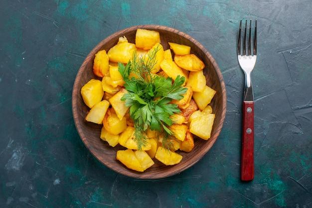 Vista de cima, batata cozida fatiada, refeição deliciosa com verduras em um prato marrom na mesa azul escura Foto gratuita