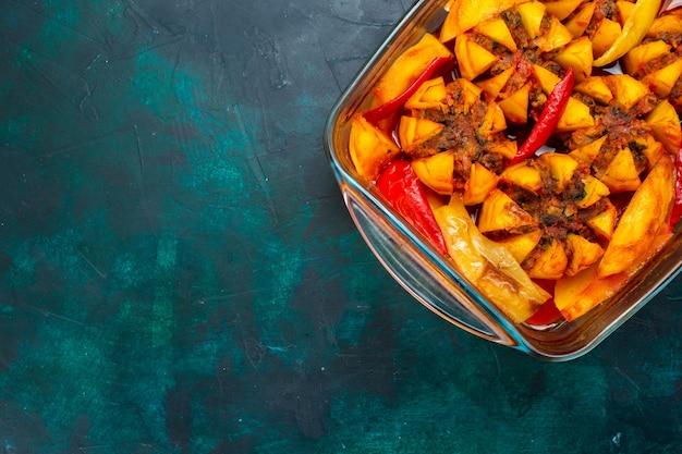 Vista de cima batatas assadas com carne picada dentro da forma no fundo azul escuro.