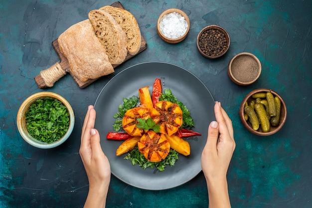 Vista de cima batatas assadas com carne picada e verduras dentro do prato com pão na mesa azul escura.