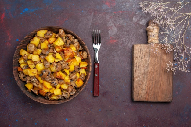 Vista de cima batatas com cogumelos, uma tigela com batatas e garfo de cogumelos e uma placa de madeira para cortar legumes