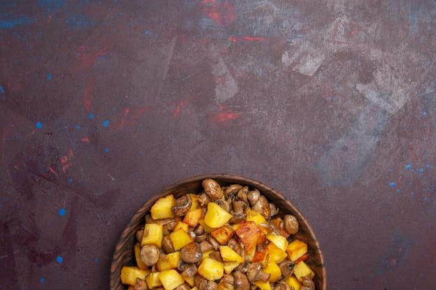Vista de cima batatas e cogumelos fritos na parte inferior da superfície escura, há batatas fritas com cogumelos em uma tigela marrom sobre uma superfície roxa