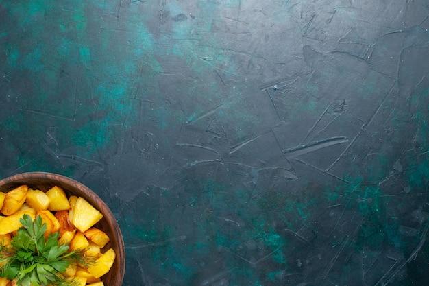 Vista de cima batatas fatiadas cozidas com verduras dentro de um prato marrom na superfície azul escura