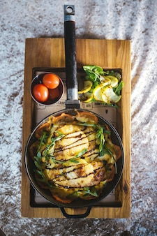 Vista de cima batatas fritas em uma frigideira com tomates em um carrinho de madeira.