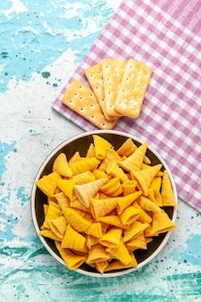 Vista de cima batatas fritas picantes com biscoitos salgados na superfície azul-claro chips cor de lanche caloria crocante