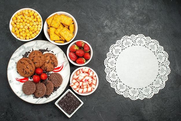 Vista de cima, biscoitos de chocolate saborosos com diferentes lanches em fundo escuro